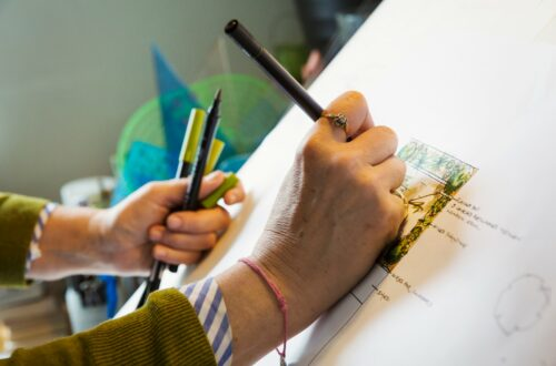 Close up of woman sitting at a drawing board, drawing with a fineliner, using a design template.